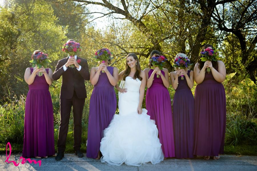 bride and bridesmaids holding flowers in front of faces