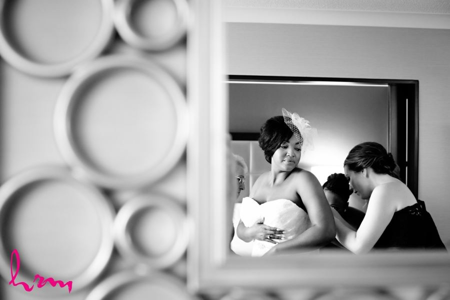 bride putting on dress in mirror