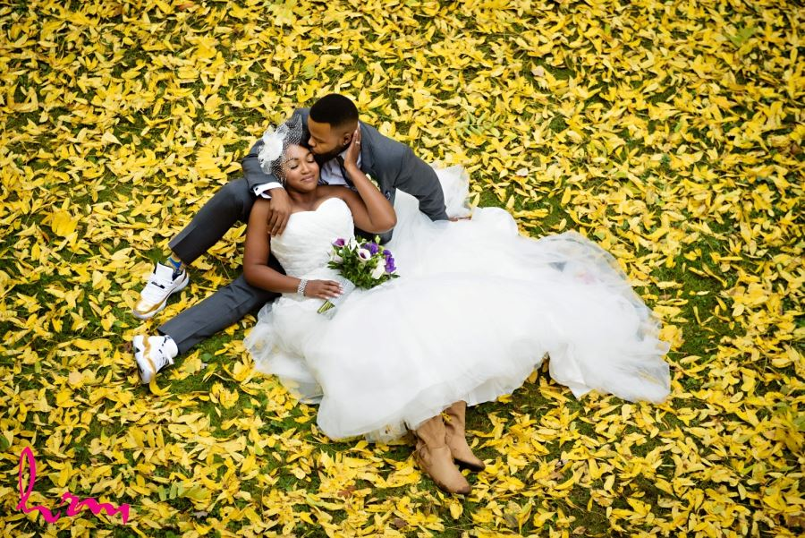 bride and groom on ground with autumn leaves