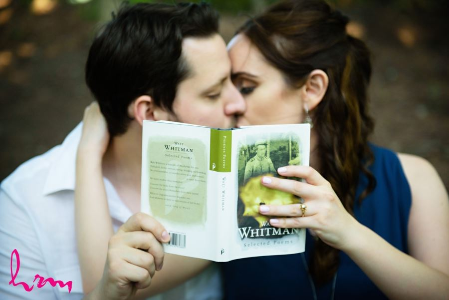 couple kissing behind book