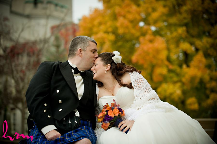 groom kissing bride outside the old courthouse in london ontario