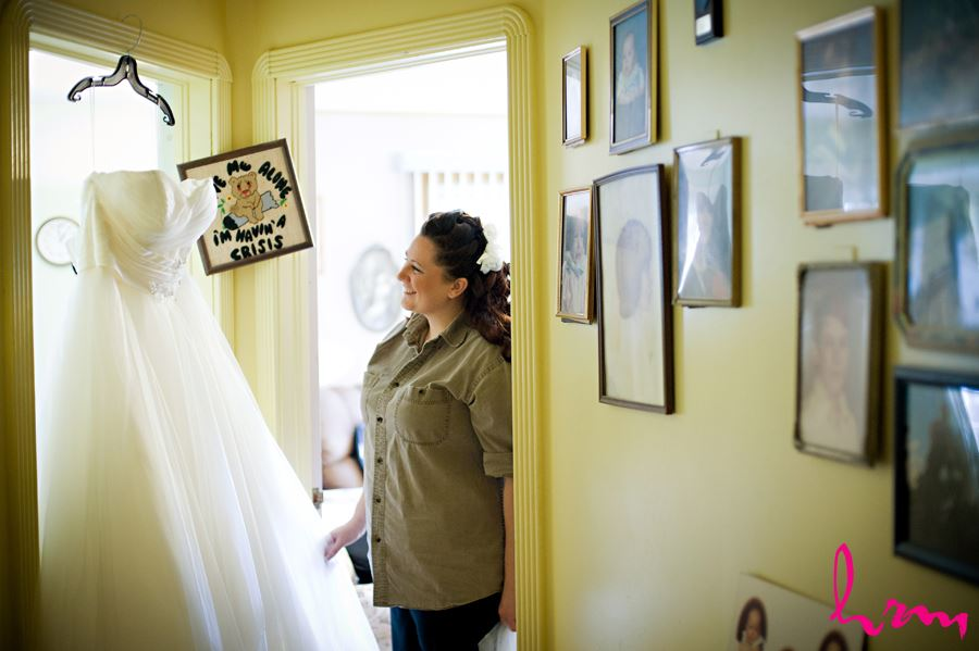 bride looking at dress before putting it on