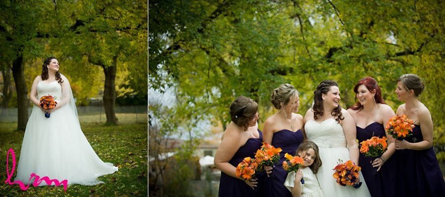 bride outside laughing with bridesmaids in front of green trees