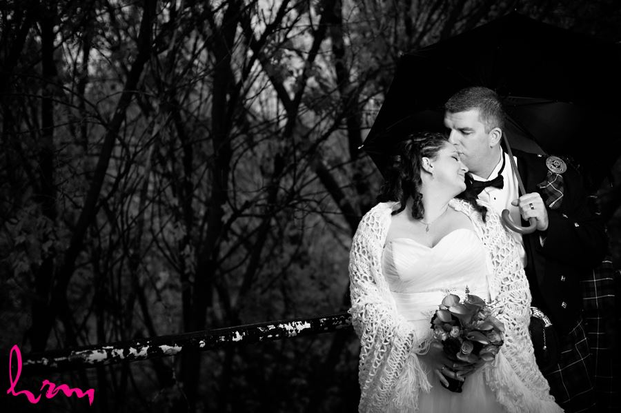 black and white groom kissing bride on head