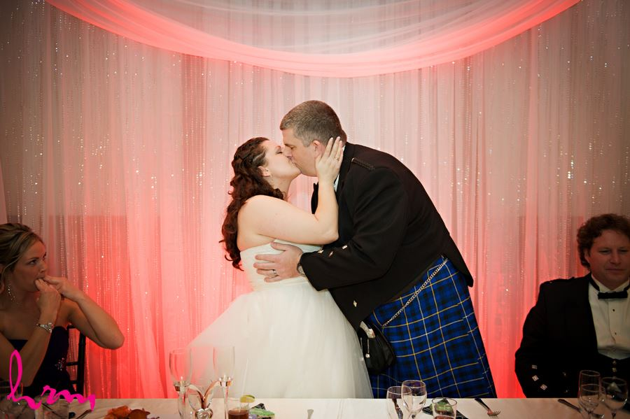 bride and groom share a kiss in the reception