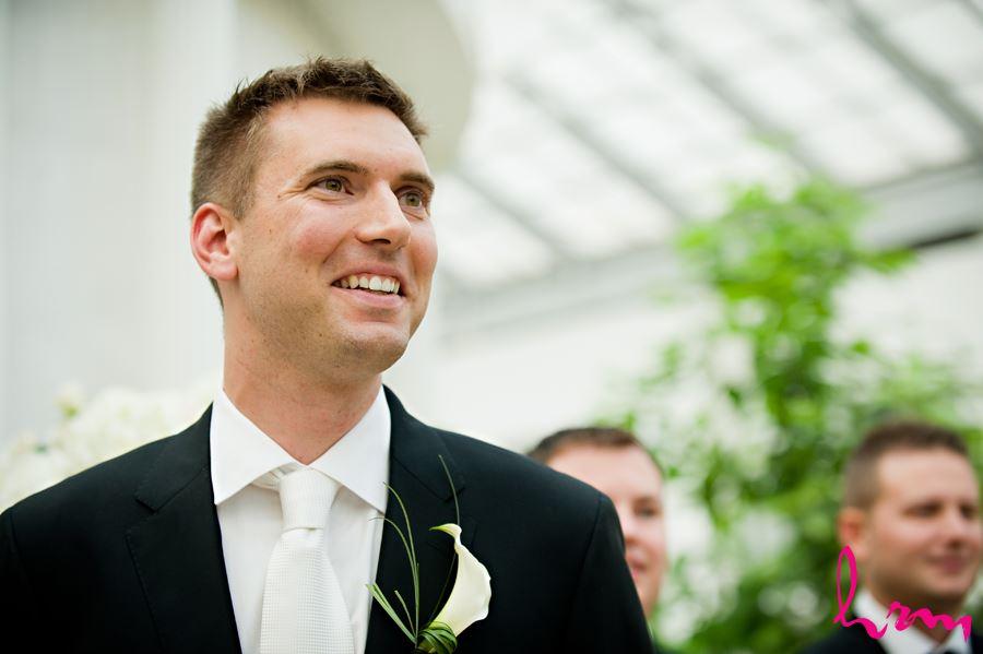 groom smiling seeing bride walking down aisle
