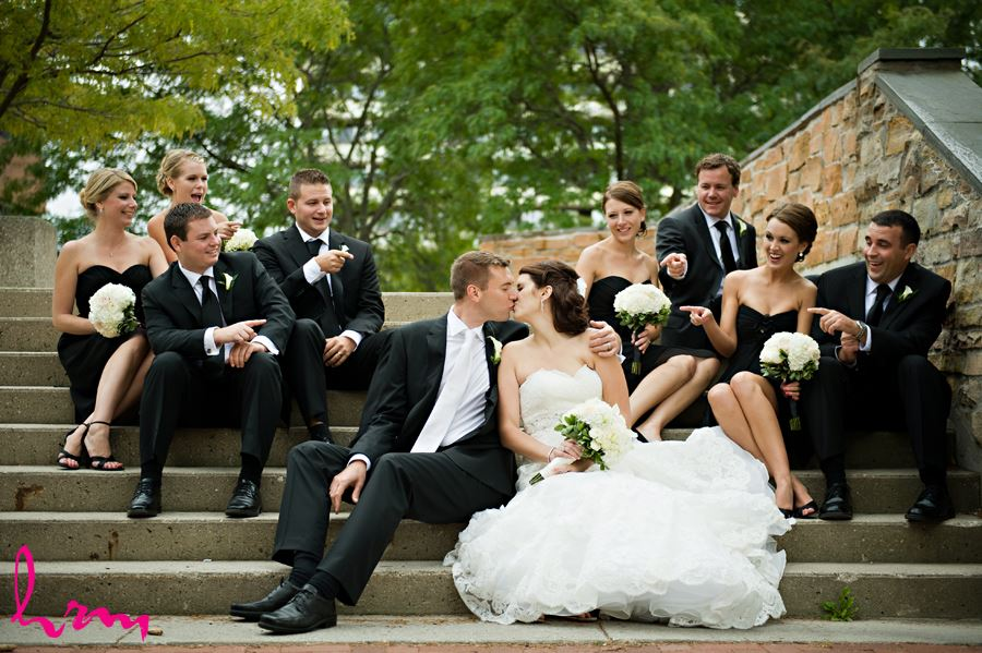wedding party on stairs and bride and groom kissing