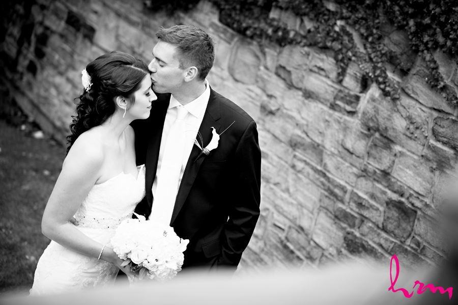 bride and groom black and white groom kissing bride on forehead