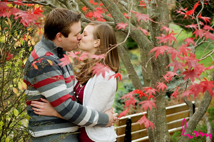 fall engagement in toronto couple kissing under red leaves