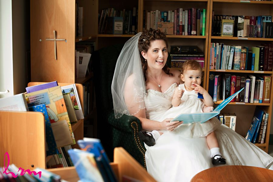 bride reading a book with flower girl before ceremony