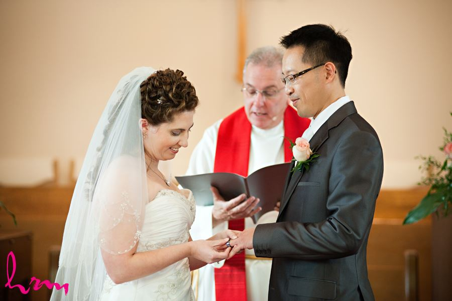 bride placing ring on grooms finger in church