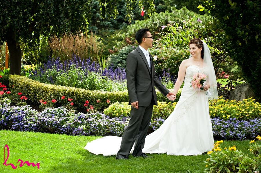bride holding grooms hand and looking at him in a flower garden