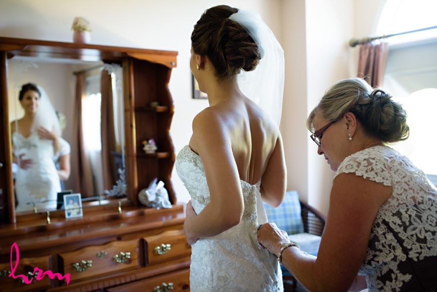 bride and mother putting on wedding dress