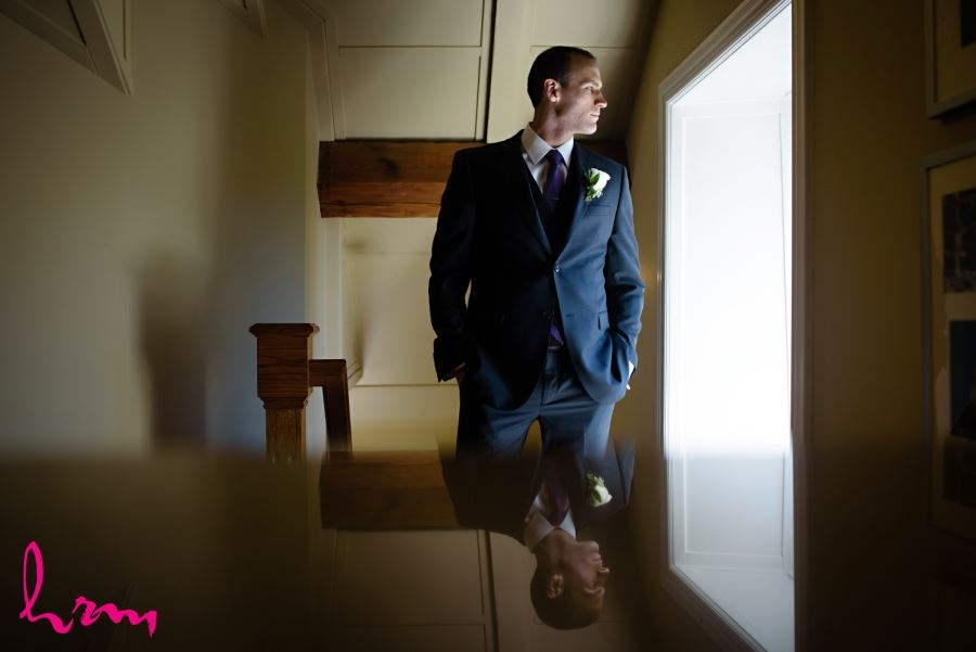 groom standing in front of window
