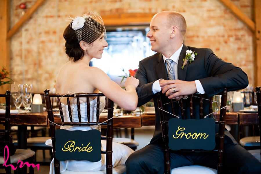 bride and groom sitting in archeo with bride and groom signs