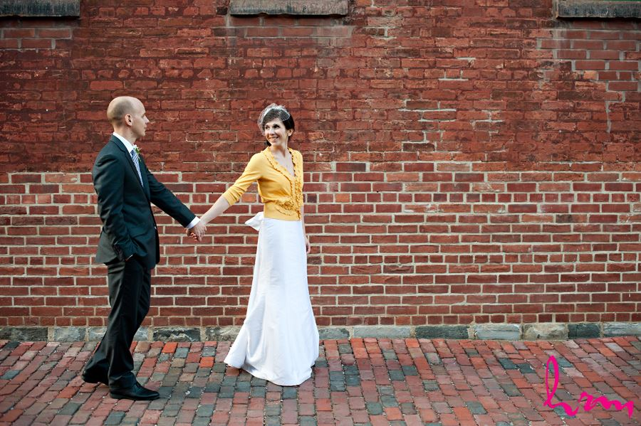 bride pulling groom walking away on brick path