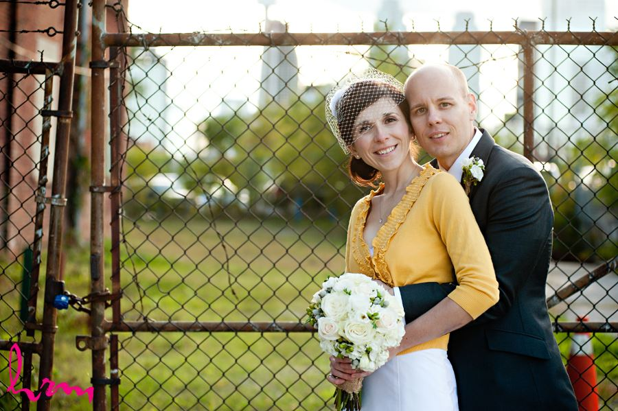 bride and groom in front of fence smiling