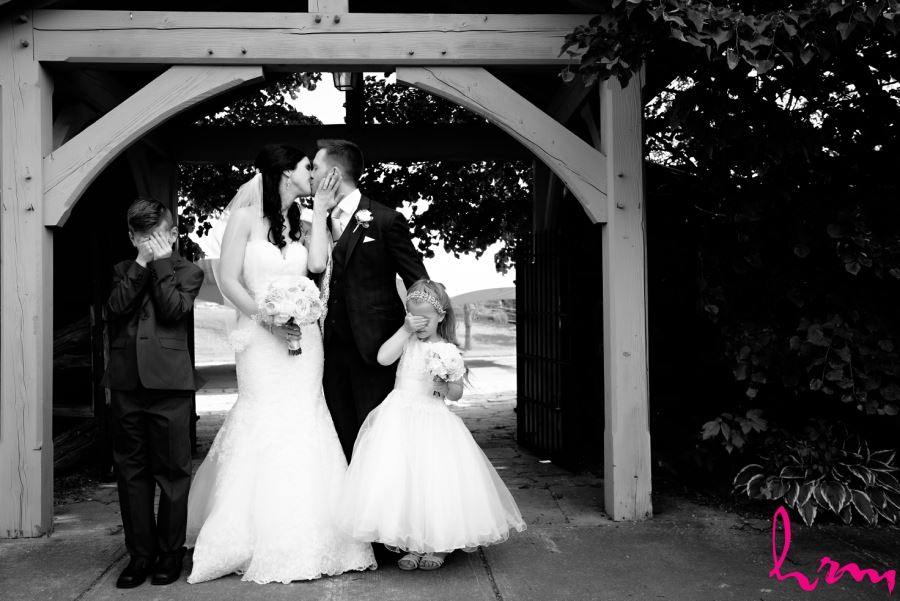 bride and groom kissing with ring bearer and flower girl