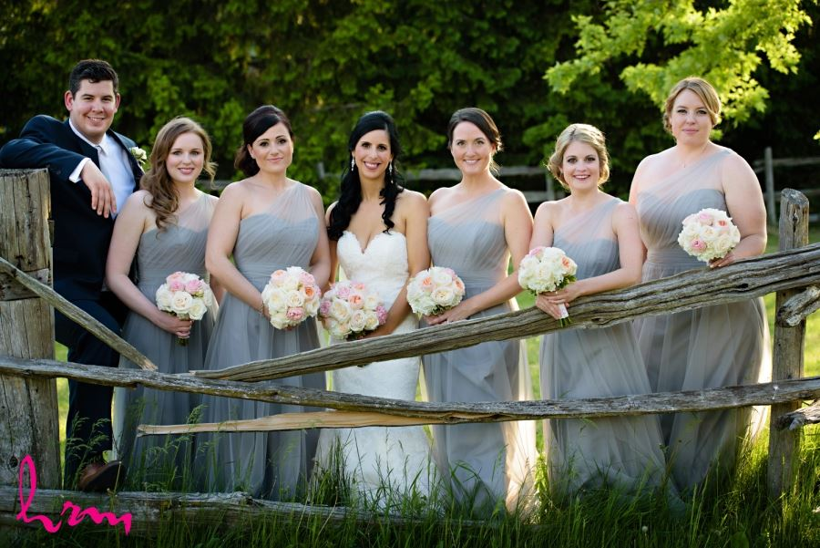 bride with bridesmaids with wooden fence