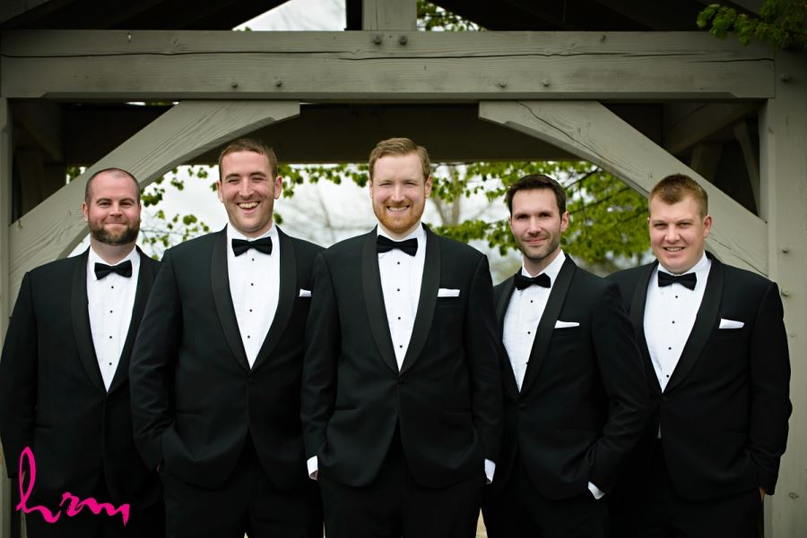 groomsmen in black suits with bow ties