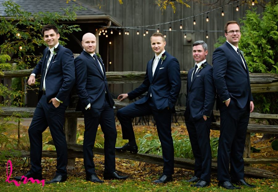 groomsmen in front of wooden fence