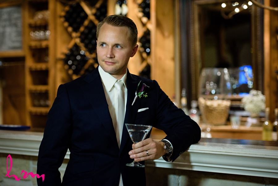 groom leaning on bar with drink