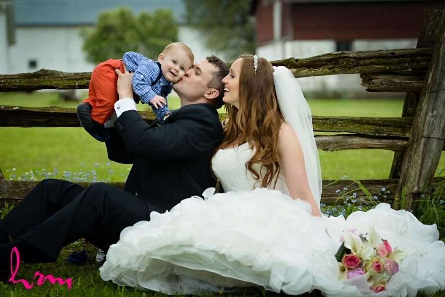 Bride and groom with baby on wedding day family