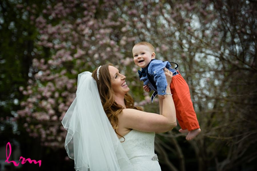 bride lifting baby in air