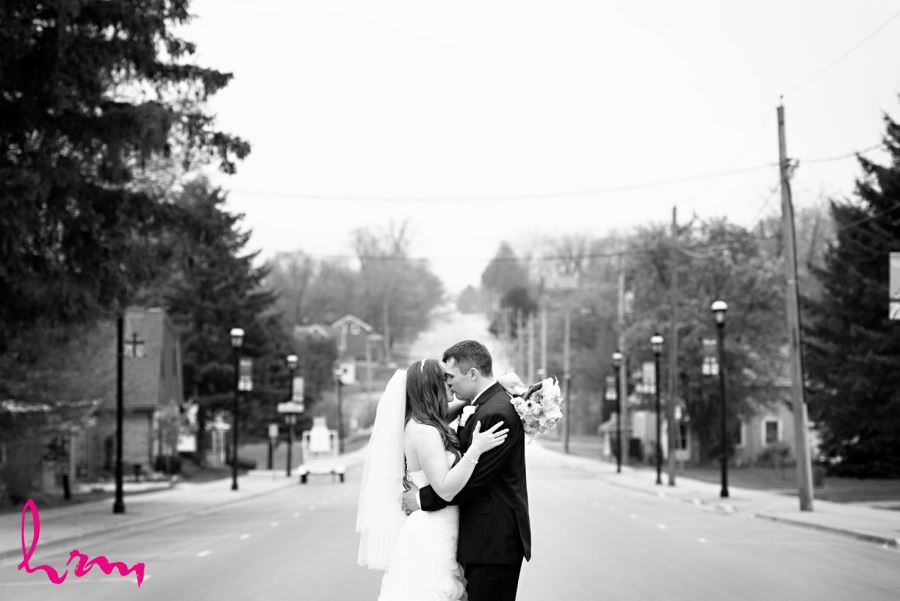 bride and groom kissing in street black and white