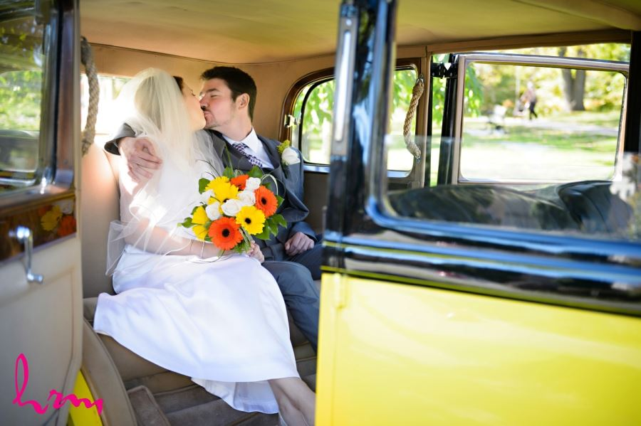 bride and groom kissing in backseat of car