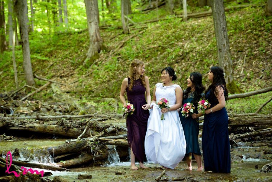 bride and bridesmaids in stream no shoes