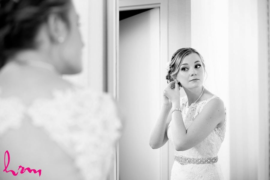 Black and white photo of bride putting in earrings taken by London Ontario wedding photographer