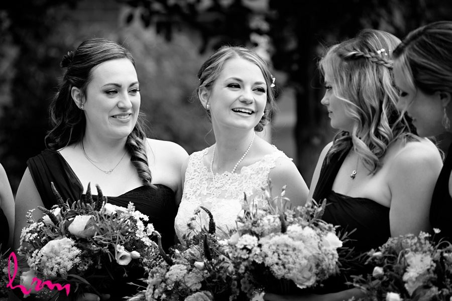 Blakc and white photo of Claude and bridesmaids holding bouquets, taken by HRM photography