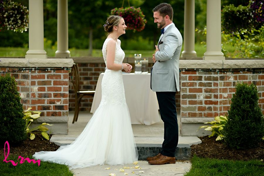 Photo of putting the ring on taken by HRM Photography London Ontario Wedding Photographer