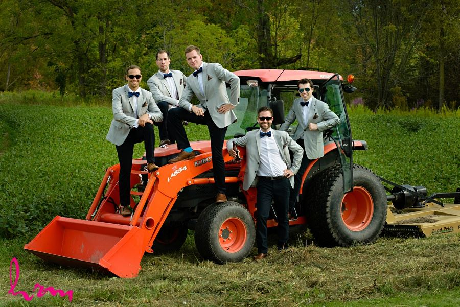 Photo of groomsmen and groom on tractor by London Ontario Wedding Photographer