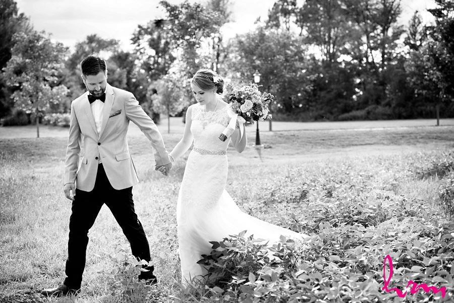 Black and white photo of bride and groom in field by London Ontario Wedding Photographer