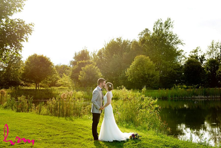 Photo of bride and groom by pond by London Ontario Wedding Photographer