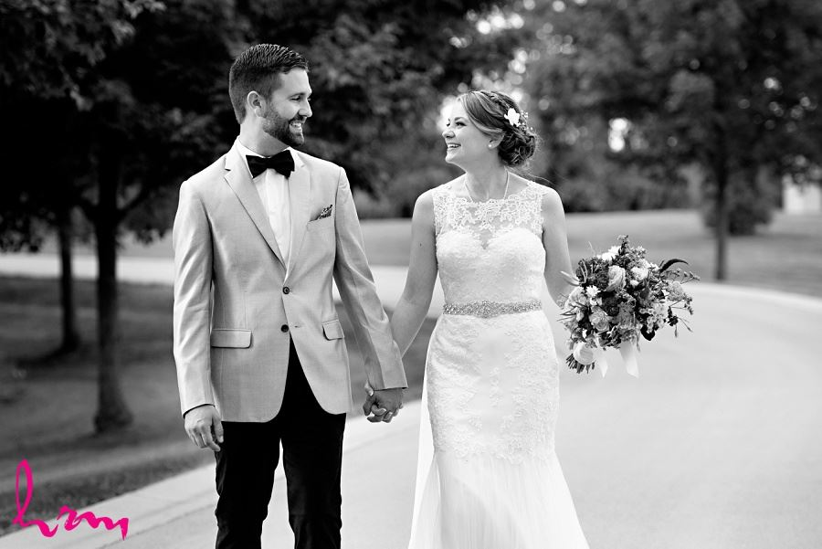 Black and white photo of bride and groom walking down road by London Ontario Wedding Photographer