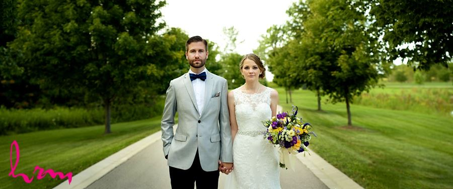 Photo of bride and groom walking down road by London Ontario Wedding Photographer