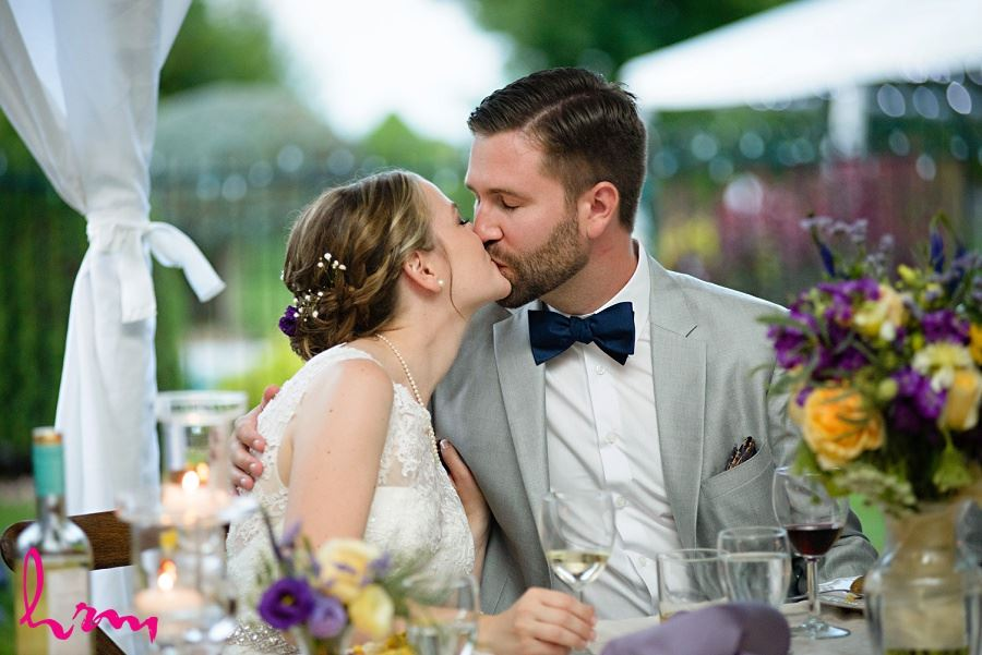 Photo of Claude and Jason kissing during toasts taken by HRM Photography