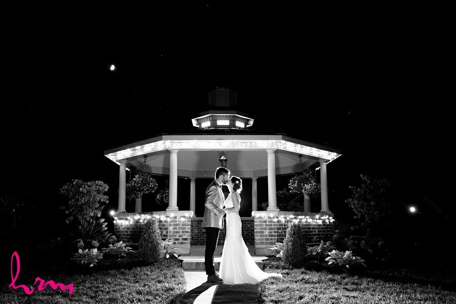 Black and white photo of bride and groom kissing at night taken by HRM Photography London Ontario wedding photographer