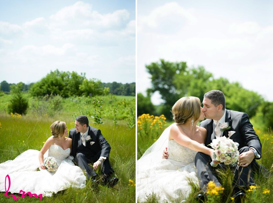 bride and groom sitting in meadow on sunny summer wedding day