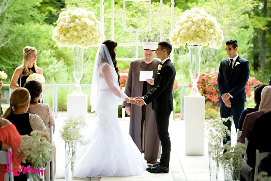 Wedding ceremony decor large bouquets at end of aisle