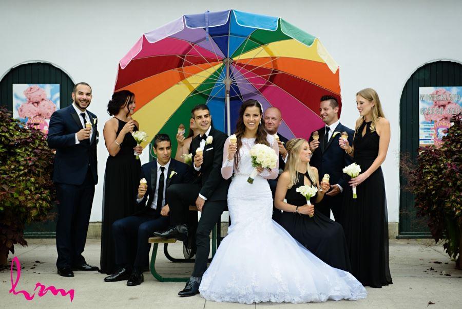 Wedding party eating ice cream with large rainbow umbrella