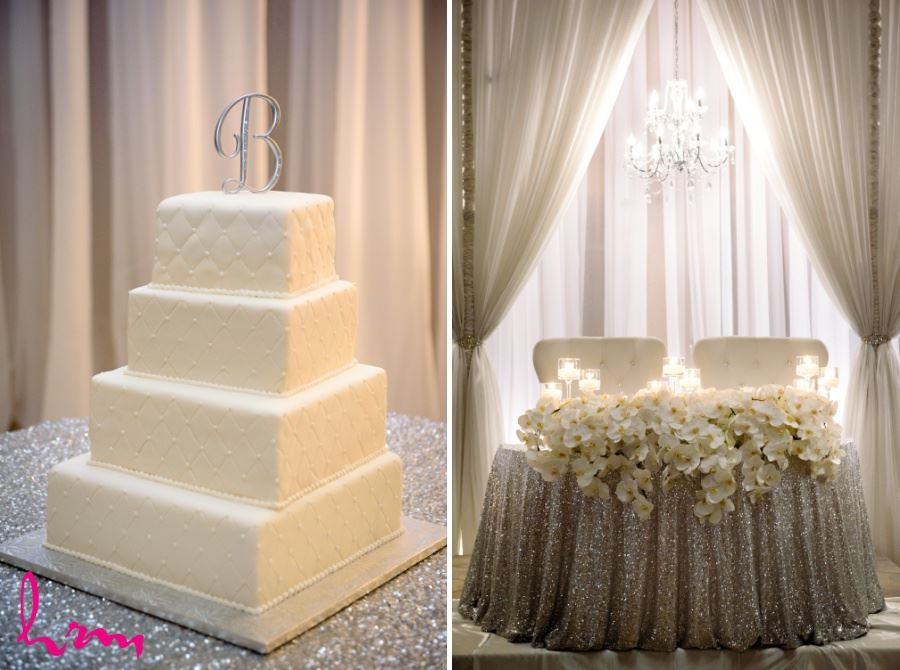 Simple white four tiered square wedding cake and orchid centrepiece head table