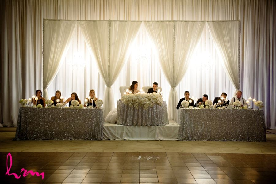 Luxurious head table with orchid cascades and sequinned table cloth