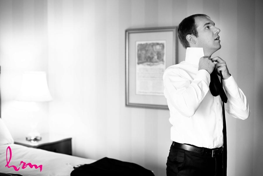 groom tying tie on wedding day black and white