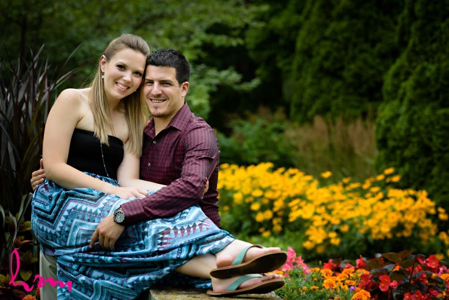 London Ontario engagement session couple sitting in front of bright flowers