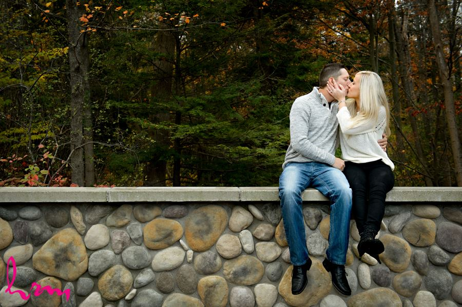 Engaged couple kissing on stone wall