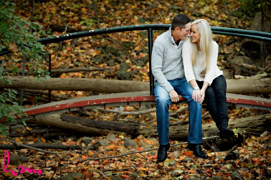 Beautiful couple cuddling on a bridge in the forest